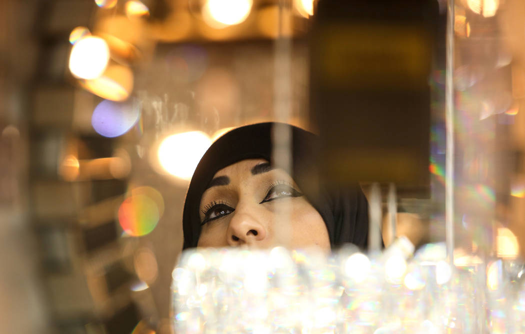 Intedhar Alzayadi looks up at a chandelier on display at the Elegant Furniture & Lighting exhibit during the opening day of the Las Vegas Winter Market held at the World Market Center in Las V ...