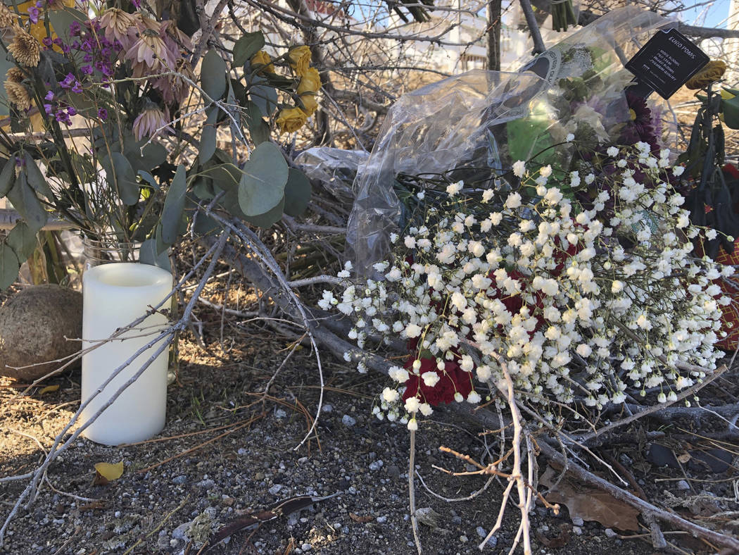 A makeshift memorial of several dozen bouquets and a candle are shown Thursday, Jan. 24, 2019, outside the south Reno, Nev., home of Gerald David, 81, and his 80-year-old wife, Sharon, whose bodie ...