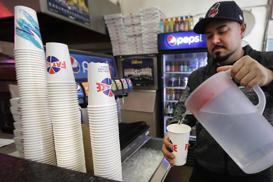 Fat Slice pizza employee Gustavo Munoz fills a cup with water Wednesday, Jan. 23, 2019, in Berkeley, Calif. (AP Photo/Ben Margot)