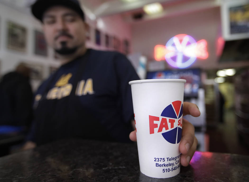 Fat Slice pizza employee Gustavo Munoz places a disposable cup on a table Wednesday, Jan. 23, 2019, in Berkeley, Calif. (AP Photo/Ben Margot)