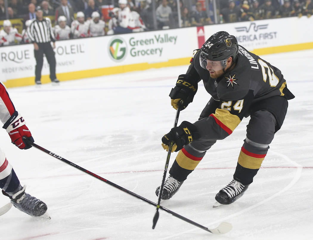 Golden Knights center Oscar Lindberg (24) sends the puck past a Washington Capitals during the first period of an NHL hockey game at T-Mobile Arena in Las Vegas on Tuesday, Dec. 4, 2018. Chase Ste ...