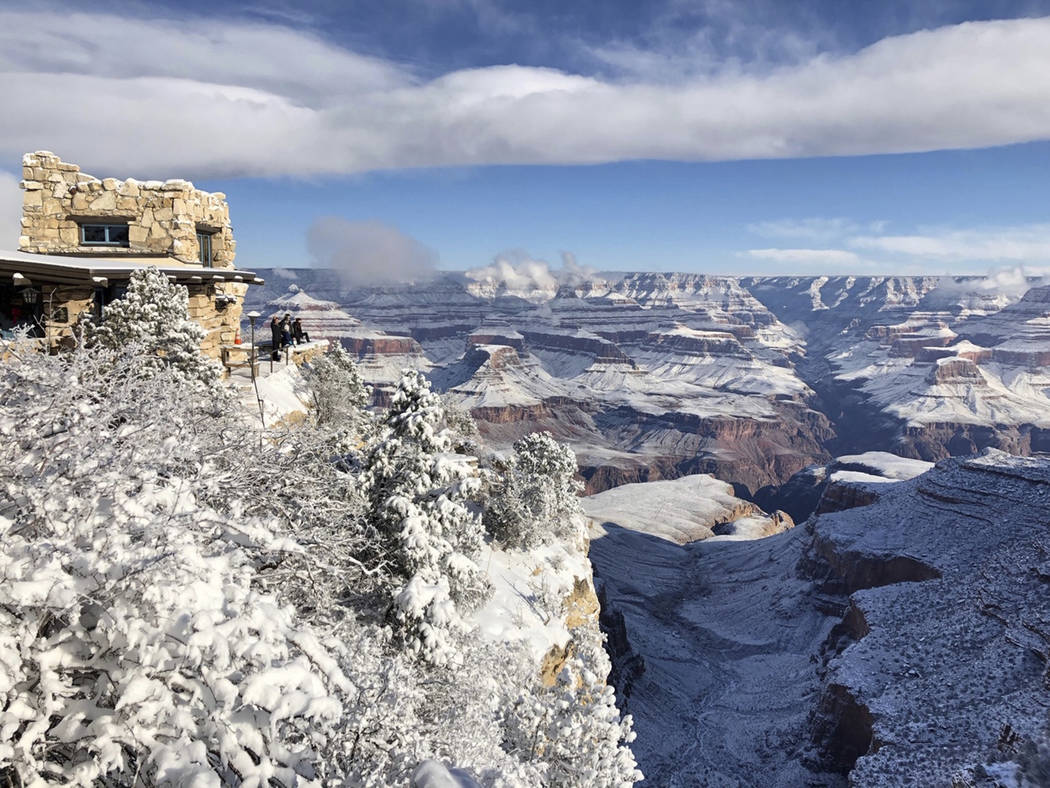 This Tuesday, Jan. 1, 2019, photo shows Lookout Studio in Grand Canyon Village on the South Rim of Grand Canyon National Park, in Arizona. A winter storm has covered cactus with snow in parts of t ...