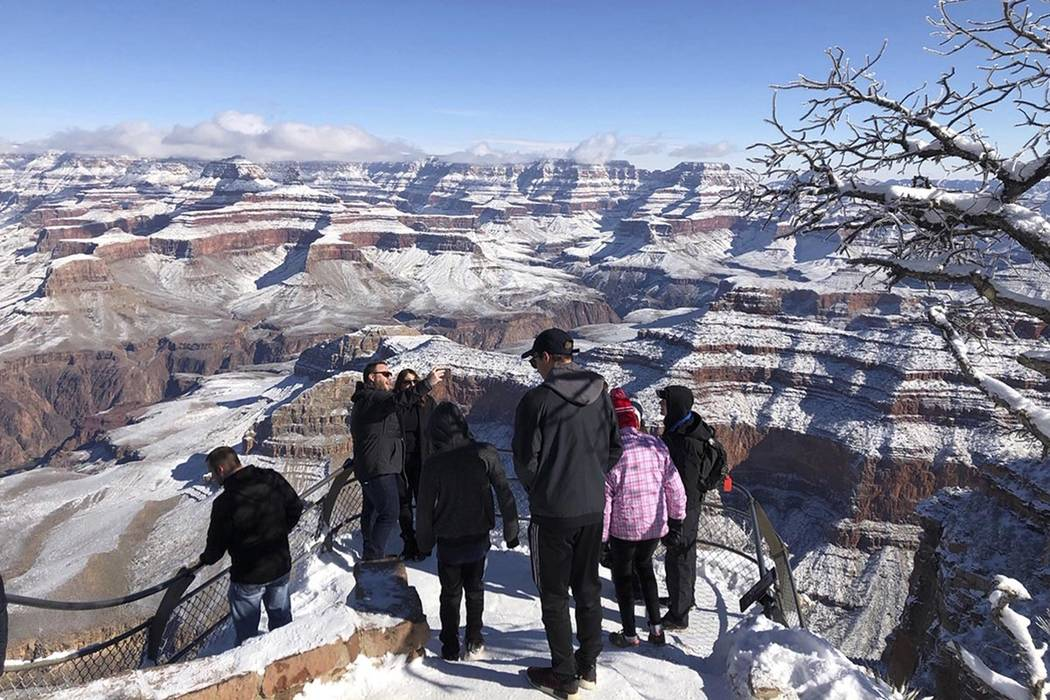Tourists look at and take photos of a snow-covered Grand Canyon in Arizona in January 2019. (AP Photo/Anna Johnson)