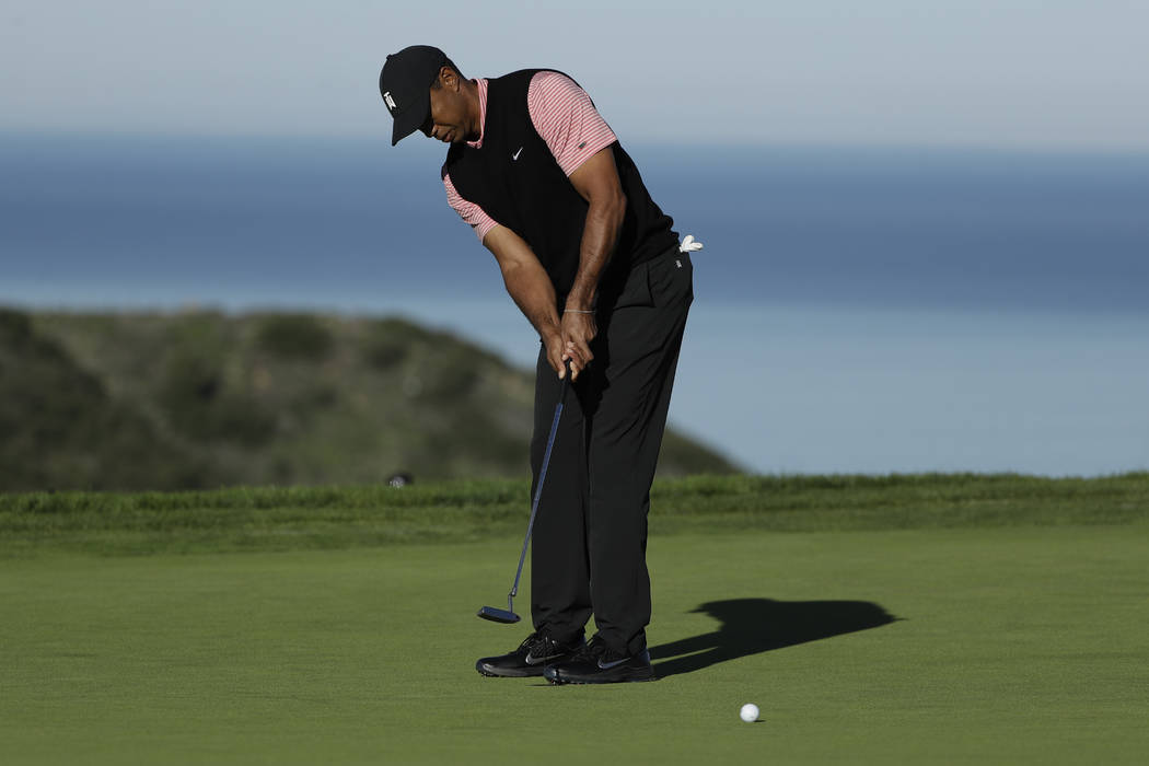 Tiger Woods putts on the 10th green of the South Course at Torrey Pines Golf Course during the final round of the Farmers Insurance golf tournament Sunday, Jan. 27, 2019, in San Diego. (AP Photo/G ...