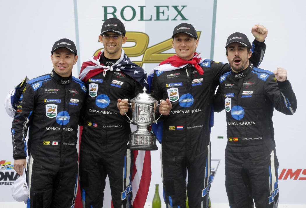 Winners of the IMSA 24 hour race, from left, Kamui Kobayashi, of Japan, Jordan Taylor, Renger Van Der Zande, of the Netherlands, and Fernando Alonso, of Spain, celebrate with the championship trop ...