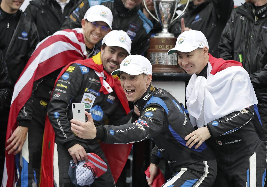 Renger Van Der Zande, second from right, of the Netherlands, takes a photo with teammates from left, Jordan Taylor, Fernando Alonso, of Spain, Van Der Zande, and Kamui Kobayashi, of Japan after wi ...
