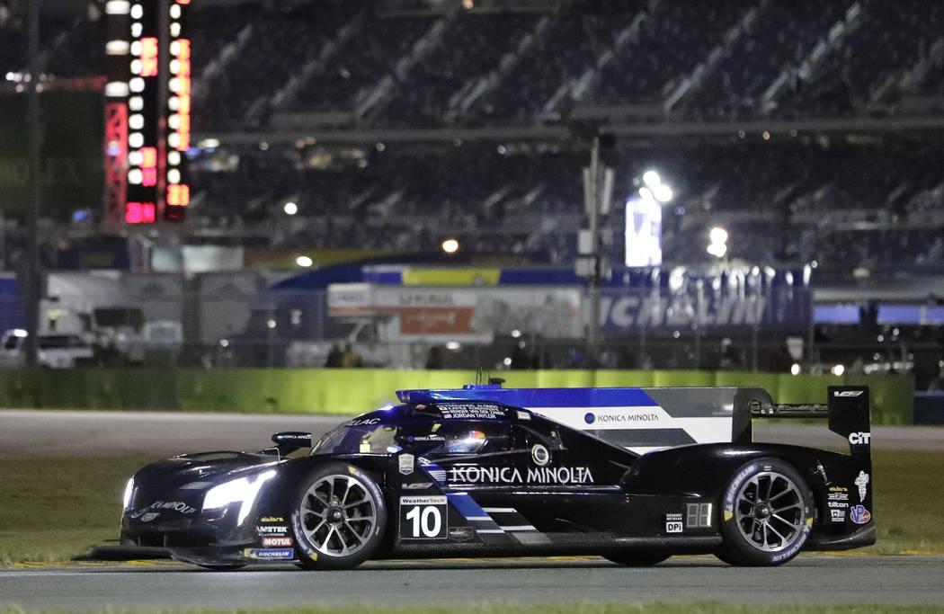 Fernando Alonso drives his Cadillac DPi during the evening hours of the IMSA 24 hour race at Daytona International Speedway, Saturday, Jan. 26, 2019, in Daytona Beach, Fla. (AP Photo/John Raoux)