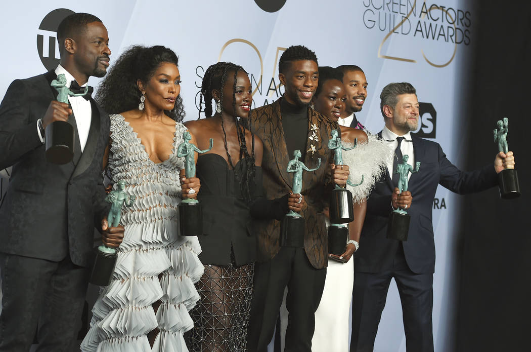 Sterling K. Brown, from left, Angela Bassett, Lupita Nyong'o, Chadwick Boseman, Danai Gurira, Michael B. Jordan, and Andy Serkis pose with the award for outstanding performance by a cast in a moti ...