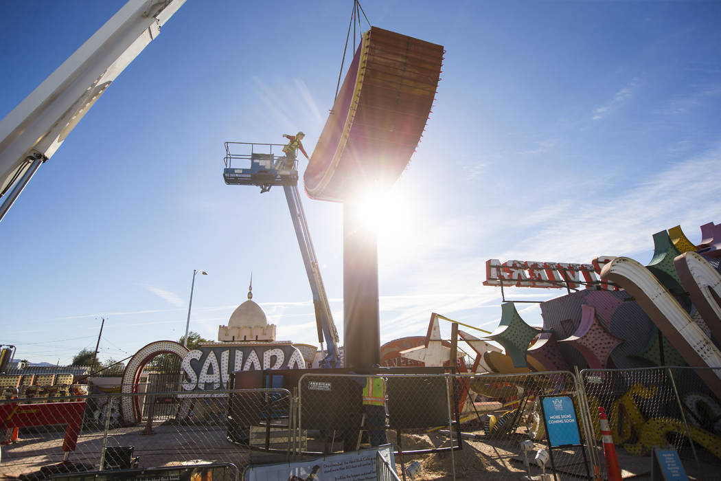 A YESCO employee on a lift guides the first piece of the Hard Rock Cafe guitar sign into place at the Neon Museum in Las Vegas on Monday, Jan. 28, 2019. Chase Stevens Las Vegas Review-Journal @css ...