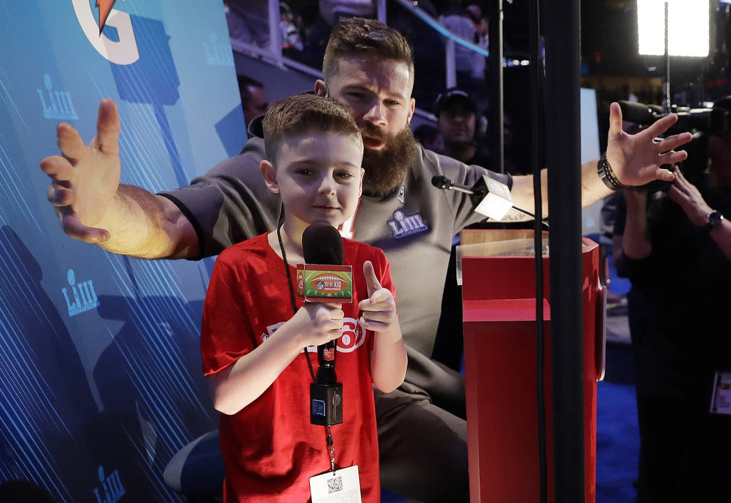 Camdyn Clancy has some fun with New England Patriots' Julian Edelman during Opening Night for the NFL Super Bowl 53 football game Monday, Jan. 28, 2019, in Atlanta. (AP Photo/David J. Phillip)