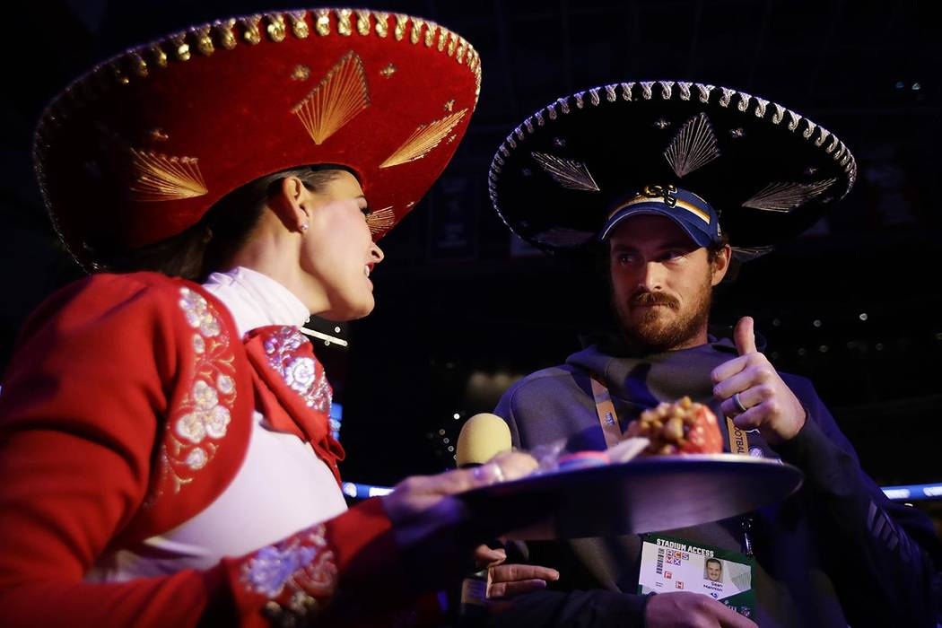 A reporter tries to get Los Angeles Rams' Sean Mannion to eat something during Opening Night for the NFL Super Bowl 53 football game, Monday, Jan. 28, 2019, in Atlanta. (AP Photo/Matt Rourke)