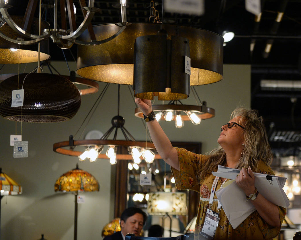 Debbie Gursley looks at the lamps on display at the CA Lighting & Accessories exhibit during the second day of the Las Vegas Market held at the World Market Center in Las Vegas, Monday, Jan. 2 ...