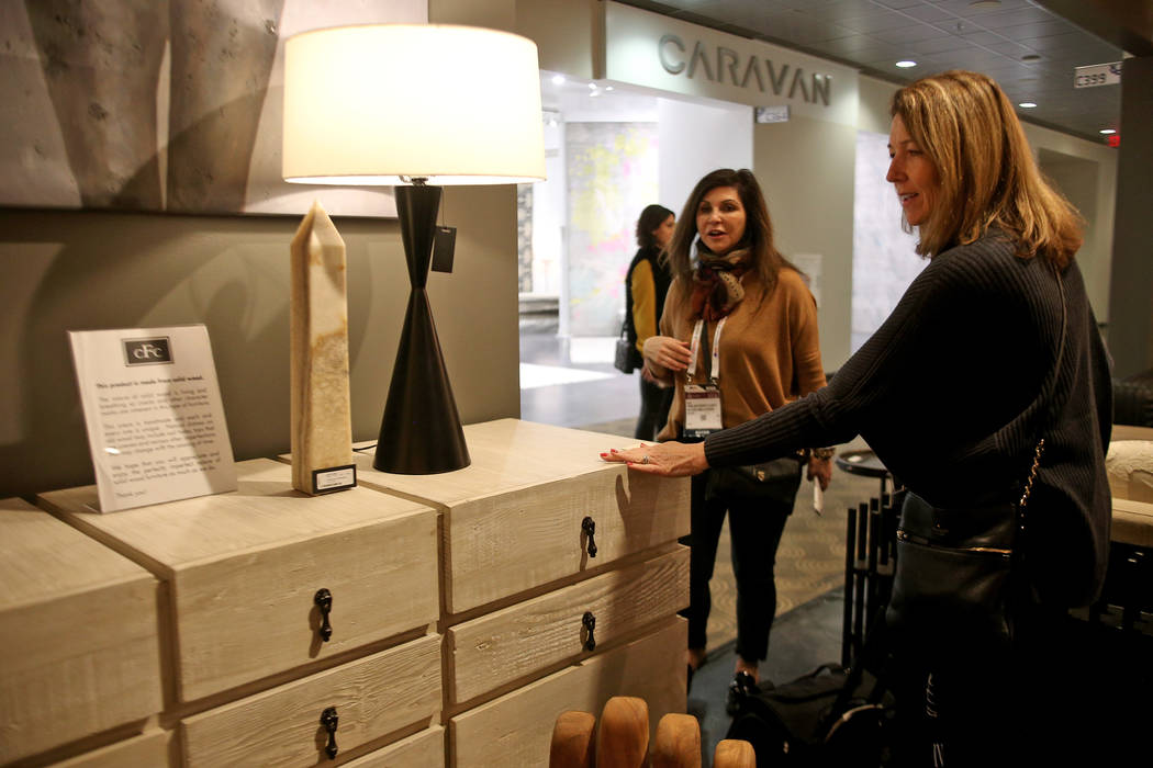 Shelley Bonelli of Los Gatos touches a solid wood cabinet with a gray wash wax on the First Look showroom tour at Las Vegas Market at the World Market Center in Las Vegas, Monday, Jan. 28, 2019. A ...