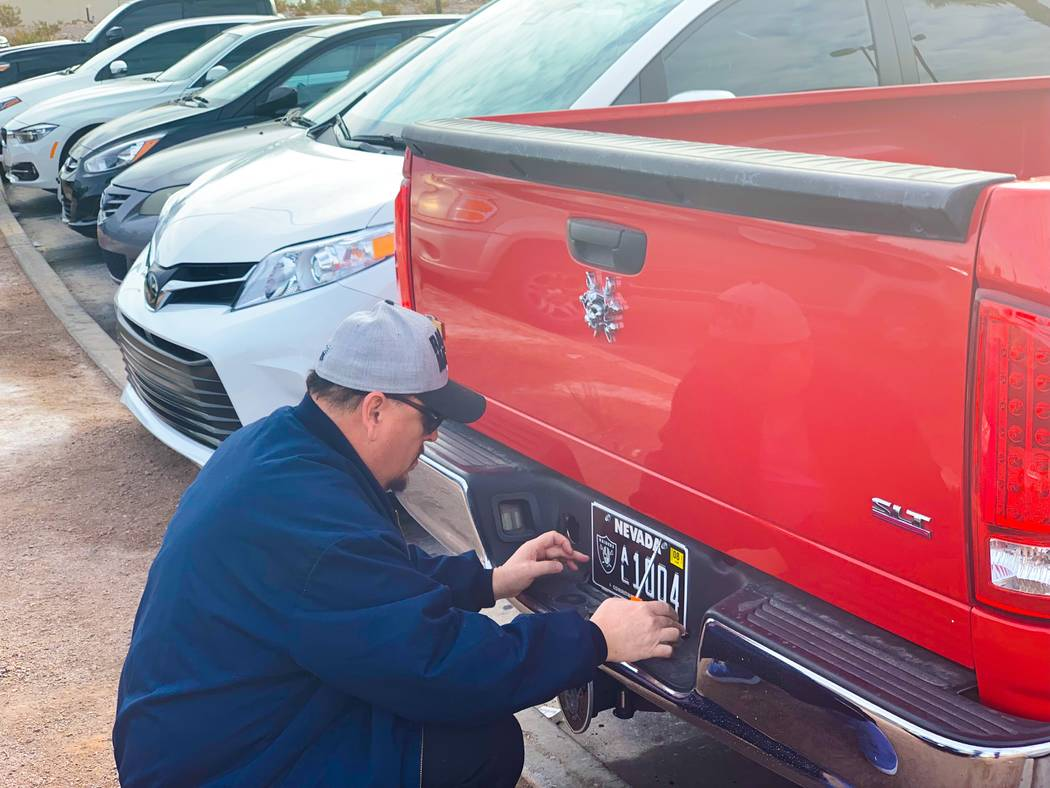 Boulder City resident Tony Cloud attaches his newly acquired Raiders Nevada specialty license plate to his pickup truck on the first day of its availability, Monday, Jan. 14, 2018. (Mick Akers/Las ...