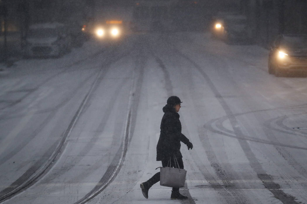 A commuter braves the wind and snow in frigid weather, Wednesday, Jan. 30, 2019, in Cincinnati. The extreme cold and record-breaking temperatures are crawling into a swath of states spanning from ...