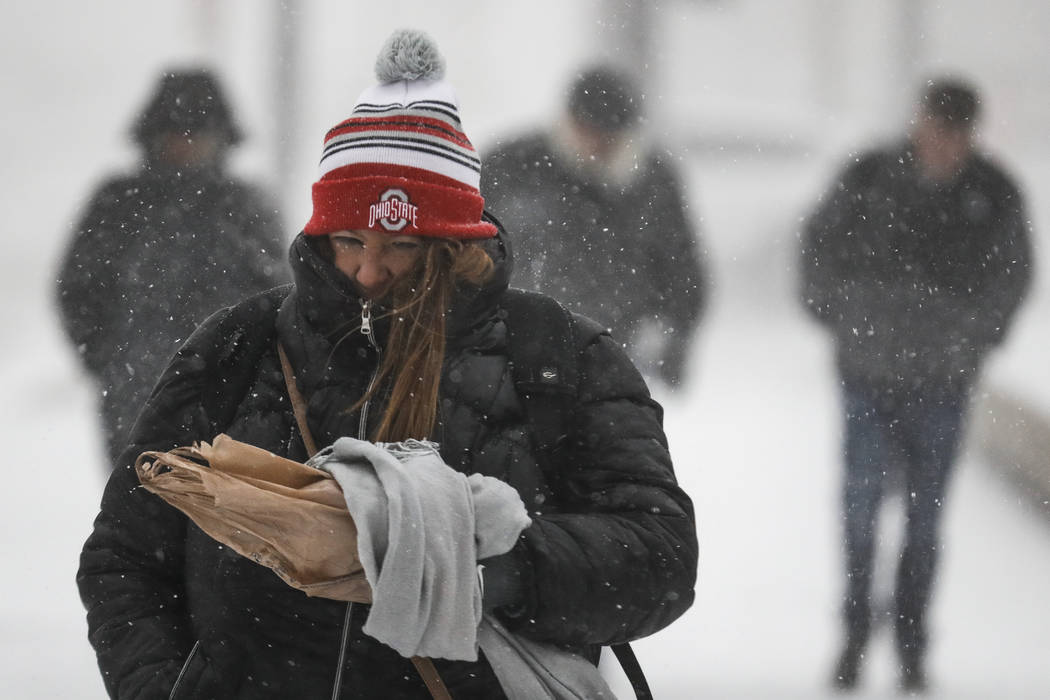 Commuters braves the wind and snow in frigid weather, Wednesday, Jan. 30, 2019, in Cincinnati. The extreme cold and record-breaking temperatures are crawling into a swath of states spanning from N ...
