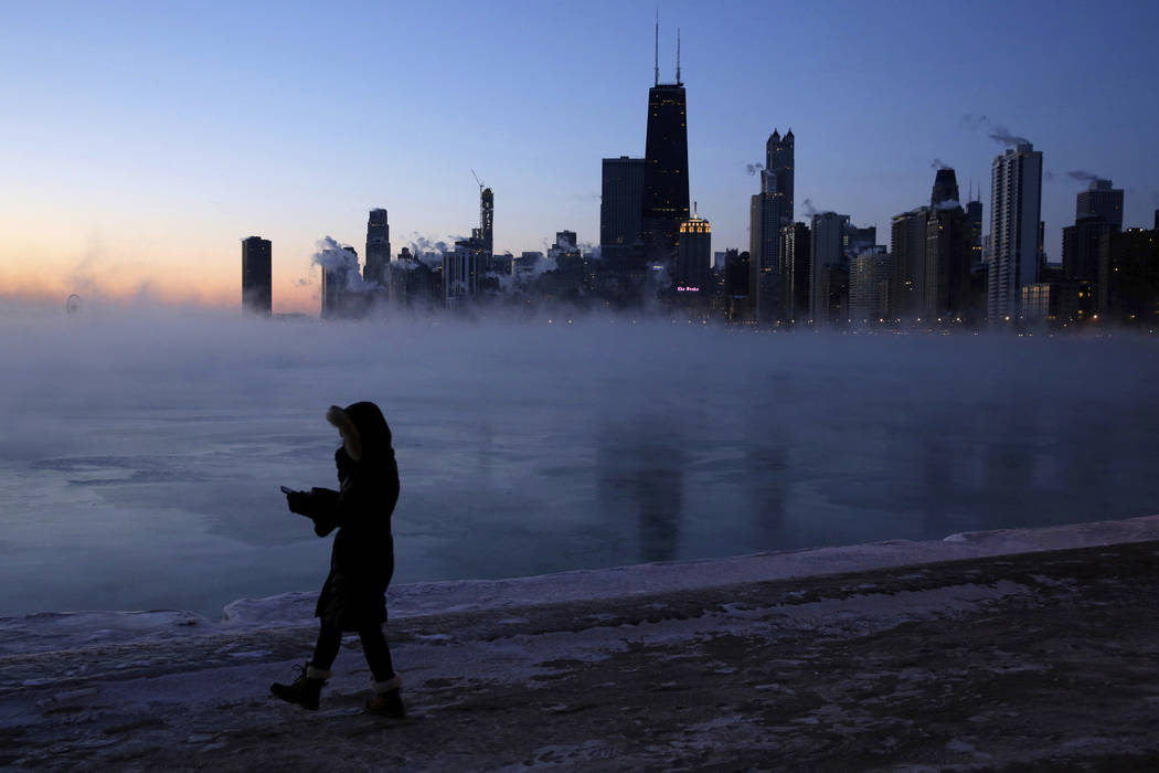 A person walks along the lakeshore, Wednesday, Jan. 30, 2019, in Chicago. A deadly arctic deep freeze enveloped the Midwest with record-breaking temperatures on Wednesday, triggering widespread cl ...