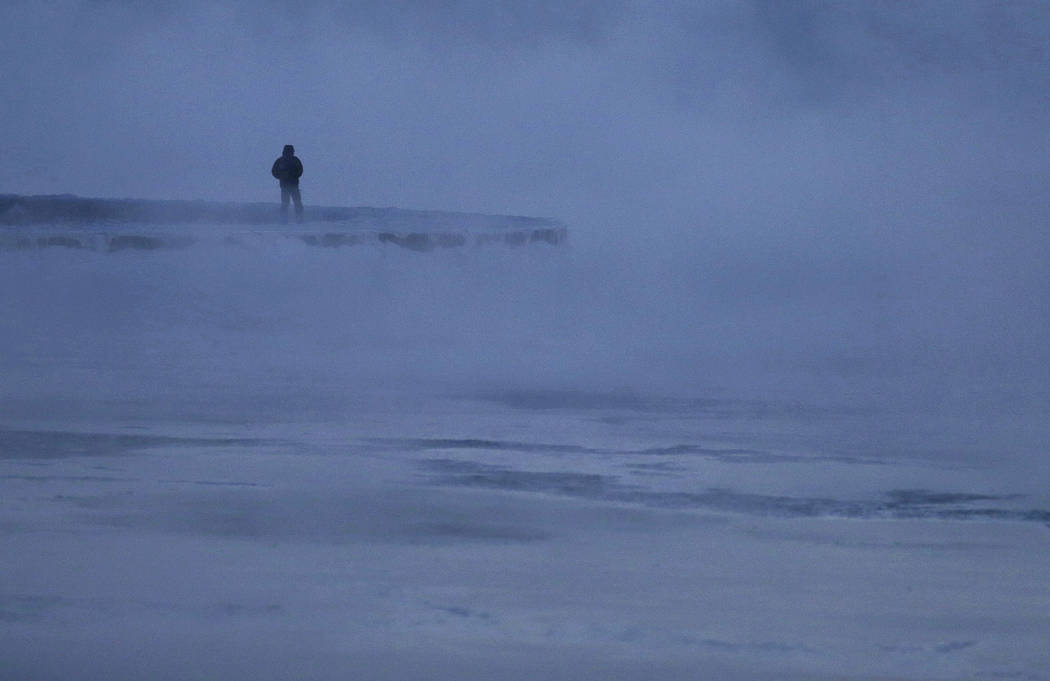 A man walks along the shore of Lake Michigan, Wednesday, Jan. 30, 2019, in Chicago. A deadly arctic deep freeze enveloped the Midwest with record-breaking temperatures on Wednesday, triggering wid ...