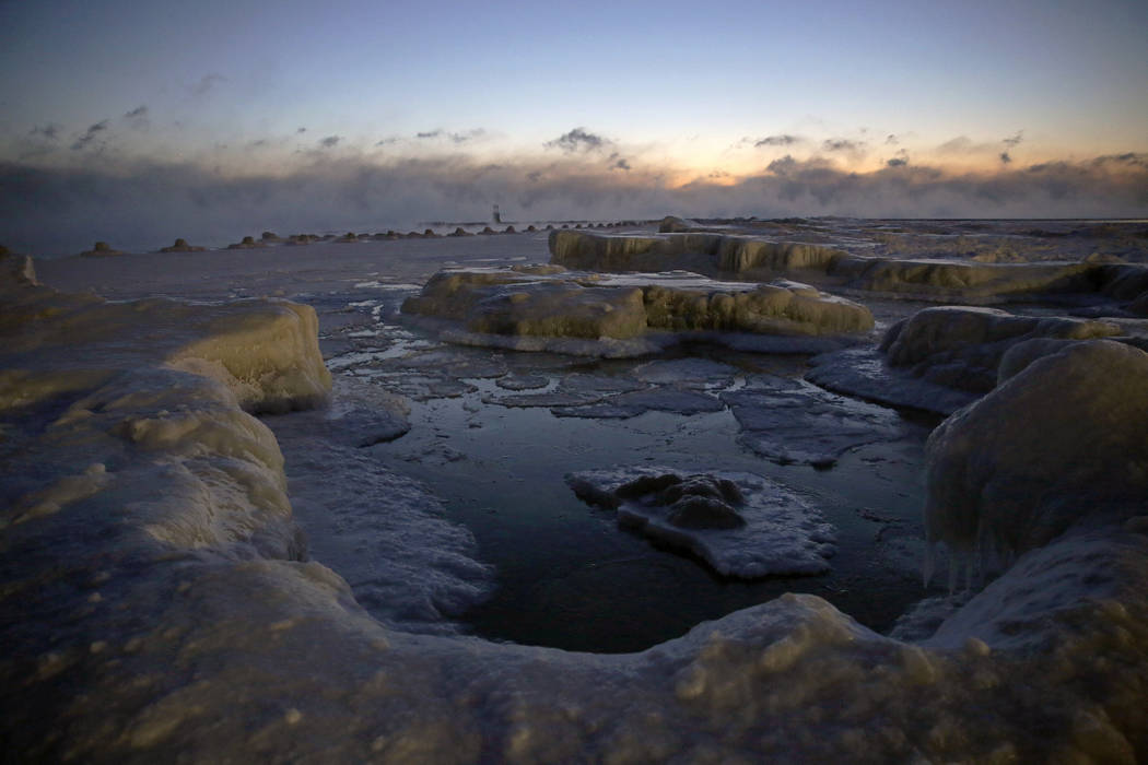 Ice forms along the shore of Lake Michigan before sunrise, Wednesday, Jan. 30, 2019, in Chicago. A deadly arctic deep freeze enveloped the Midwest with record-breaking temperatures on Wednesday, t ...