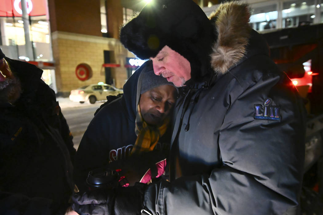 Pastor John Steger, with Grace In The City church, embraces Jearline Cyrus, a homeless woman, in downtown Minneapolis, Tuesday, Jan. 29, 2019, while delivering cold-weather gear, hot chocolate and ...