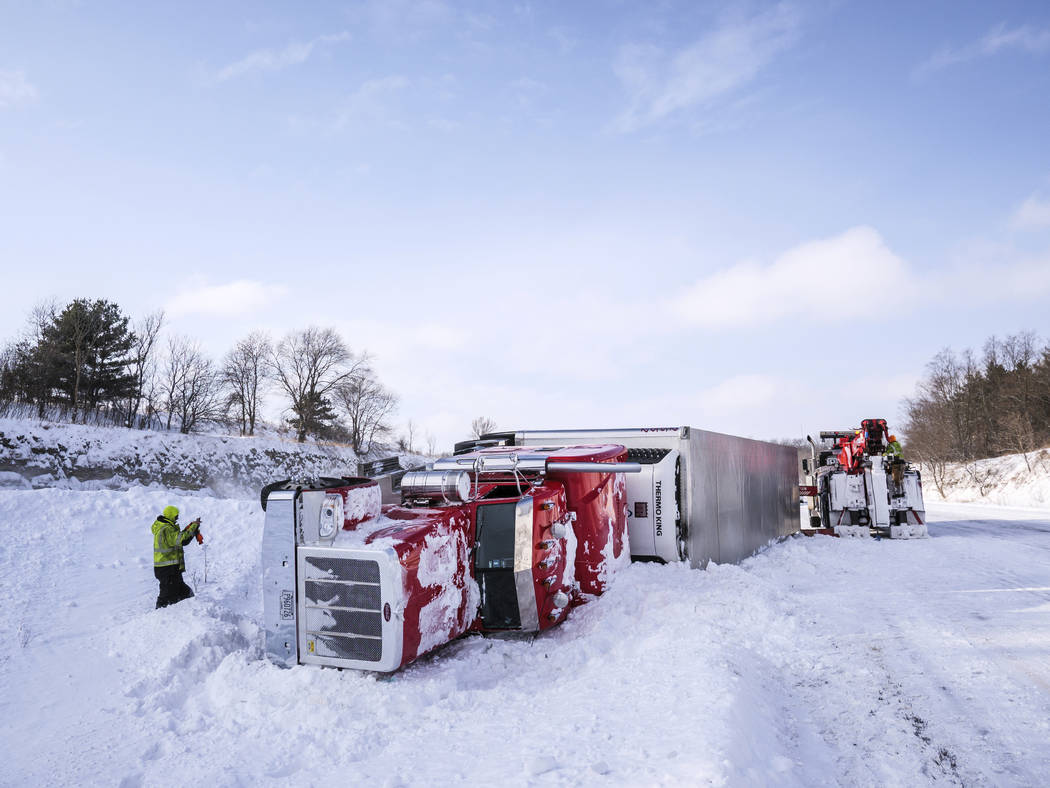 Tow truck personnel work to remove an overturned semi in the median of Interstate 90 at mile marker 218 near the U.S. Highway 52 exit Monday, Jan. 28, 2019, southeast of Rochester, Minn. According ...