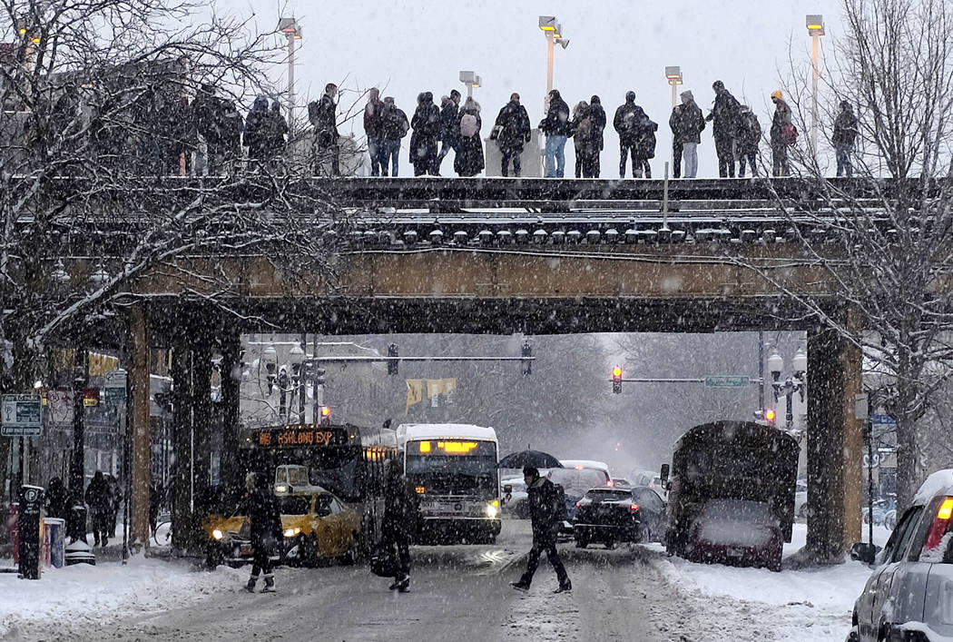 Commuters wait for a train as snow falls Monday, Jan. 28, 2019, in Chicago. The plunging temperatures expected later this week that have forecasters especially concerned. Wind chills could dip to ...