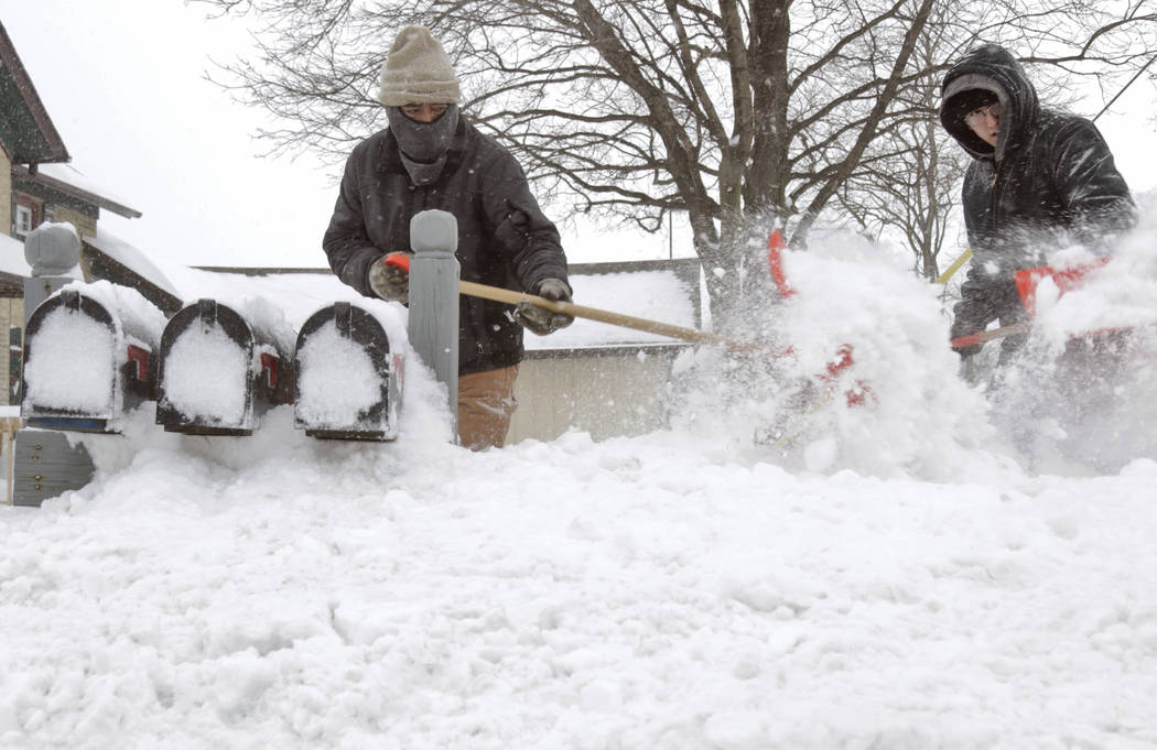 Ausencio Castaneda of Kewaskum, left, clears a path to a series of mailboxes outside a multi-family home with his son Ausencio Castaneda Jr. onMonday, Jan. 28, 2019, in Kewaskum, Wis. A number of ...