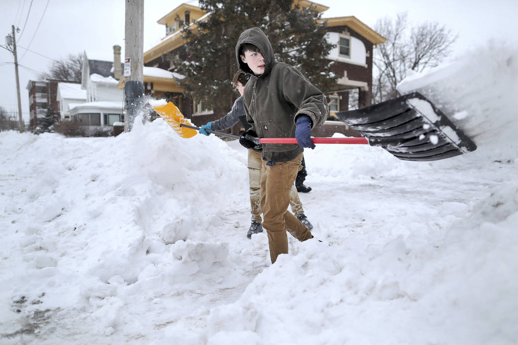Nathan Tearman, front center, gets help from his brother James as they shovel the driveway of their home on Monday, Jan. 28, 2019, after a winter snowstorm made its way through Janesville, Wis. De ...