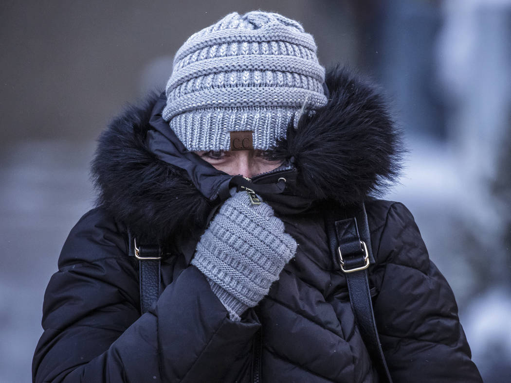 Andrea Billings keeps her face covered while walking across Center Street at its intersection with 1st Avenue in subzero temperatures on the way to her car after work Tuesday, Jan. 29, 2019, in do ...