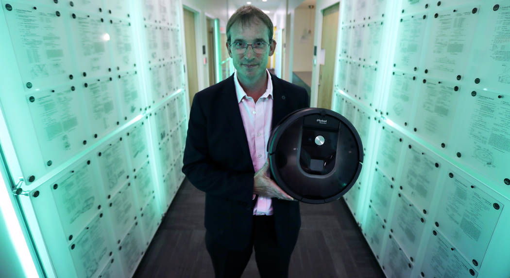 FILE - In this Thursday, Aug. 25, 2016, file photo, iRobot co-founder and CEO Colin Angle is illuminated in blue-green light while holding a Roomba vacuum in a hallway decorated in patents the com ...