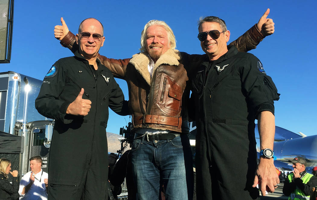 """Richard Branson center celebrates with pilots Rick """"CJ"""" Sturckow, left, and Mark """"Forger"""" Stucky, right, after Virgin Galactic's tourism spaceship climbed more t ..."""