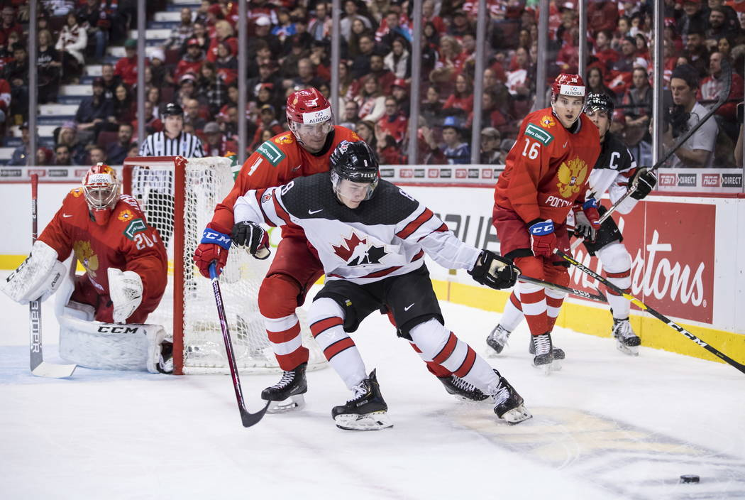 Canada's Cody Glass (8) reaches for the puck while being checked by Russia's Alexander Alexeyev during the second period of a world junior hockey championships game in Vancouver, British Columbia, ...