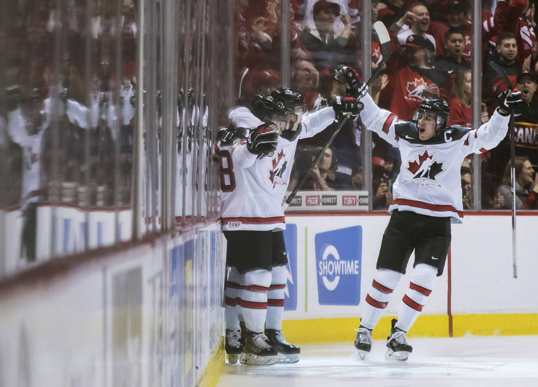 Canada's Markus Phillips, Cody Glass and Maxime Comtois, from left, celebrate Glass' goal against Russia during the first period of a world junior hockey championships game in Vancouver, British C ...