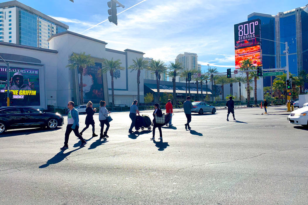 Pedestrians cross Las Vegas Boulevard at Sahara Avenue Wednesday, Jan. 30, 2019, where a planned group of pedestrian bridges are slated to be built. (Mick Akers/Las Vegas-Review Journal)