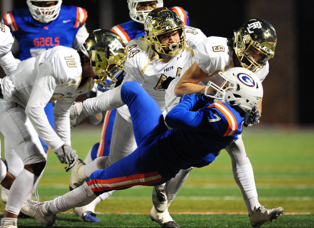Bishop Gorman running back Biaggio Ali Walsh (7) is tackled by the Faith Lutheran defense in the first half of their prep football game at Bishop Gorman High School in Las Vegas Friday, Nov. 18, 2 ...