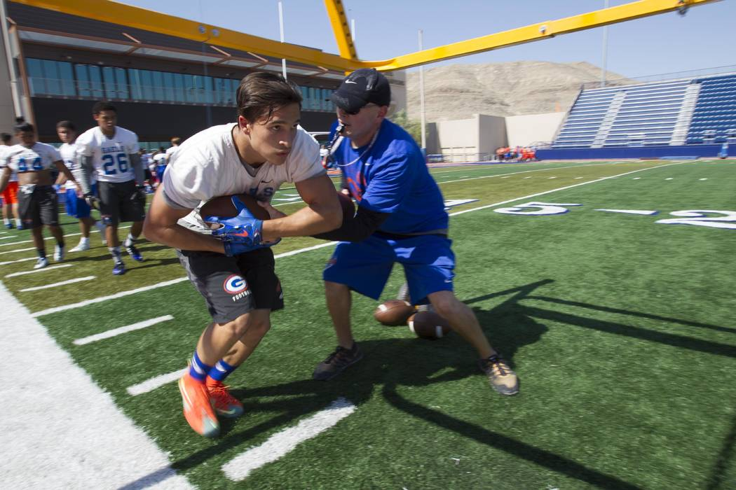 Bishop Gorman running back Biaggio Ali Walsh, left, (7) takes a football from a coach as he runs a drill during team practice at Bishop Gorman High School in Las Vegas on Wednesday, July 23, 2016. ...