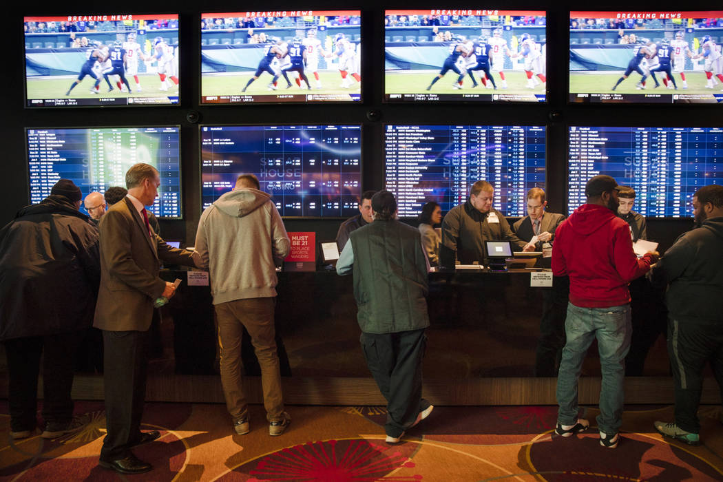 In this Thursday, Dec. 13, 2018, file photo, gamblers place bets in the temporary sports betting area at the SugarHouse Casino in Philadelphia. (AP Photo/Matt Rourke, File)