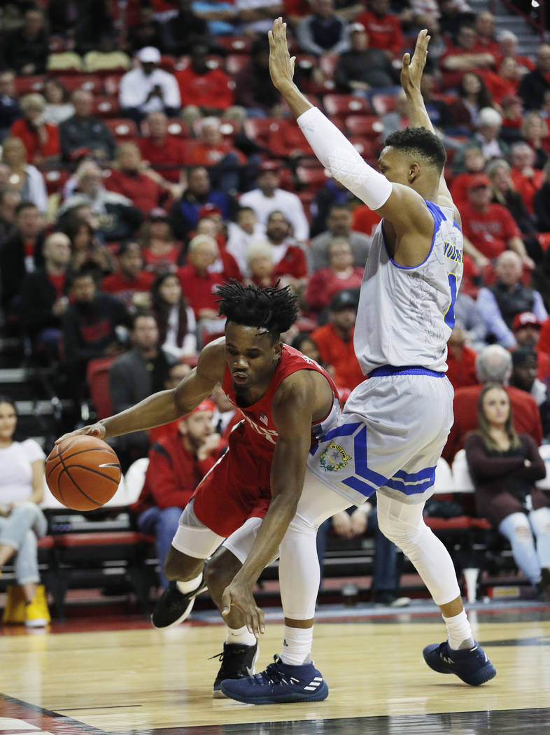 UNR's Tre'Shawn Thurman, right, fouls UNLV's Joel Ntambwe during the first half of an NCAA college basketball game Tuesday, Jan. 29, 2019, in Las Vegas. (AP Photo/John Locher)