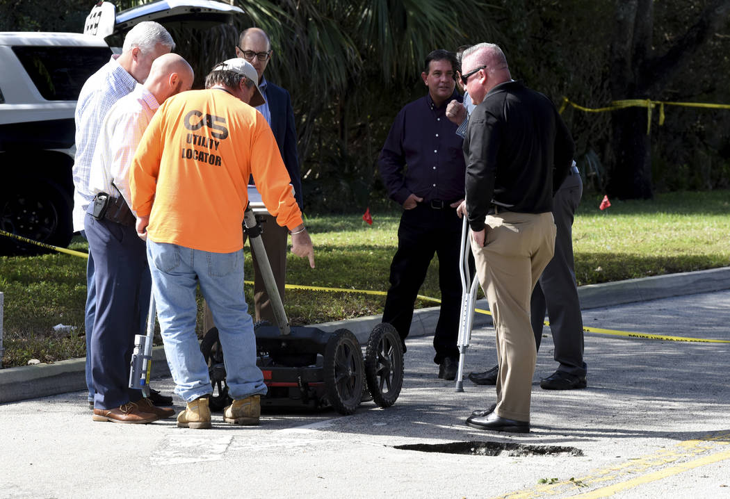 FBI and Pembroke Pines Police look at a tunnel by a possible would-be bank robber which was discovered beneath the entrance to the Flamingo Pines shopping plaza Wednesday, Jan. 30, 2019, in Pembro ...