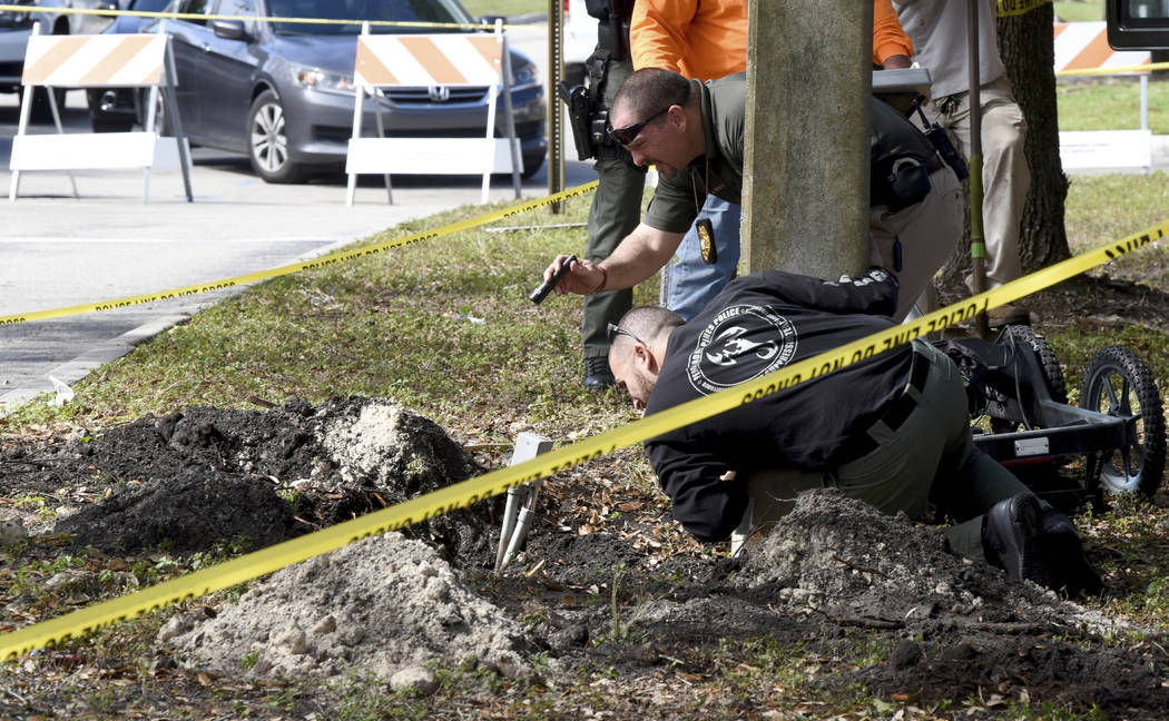 FBI and Pembroke Pines Police investigate a tunnel by a possible would-be bank robber which was discovered beneath the entrance to the Flamingo Pines shopping plaza Wednesday, Jan. 30, 2019, in Pe ...