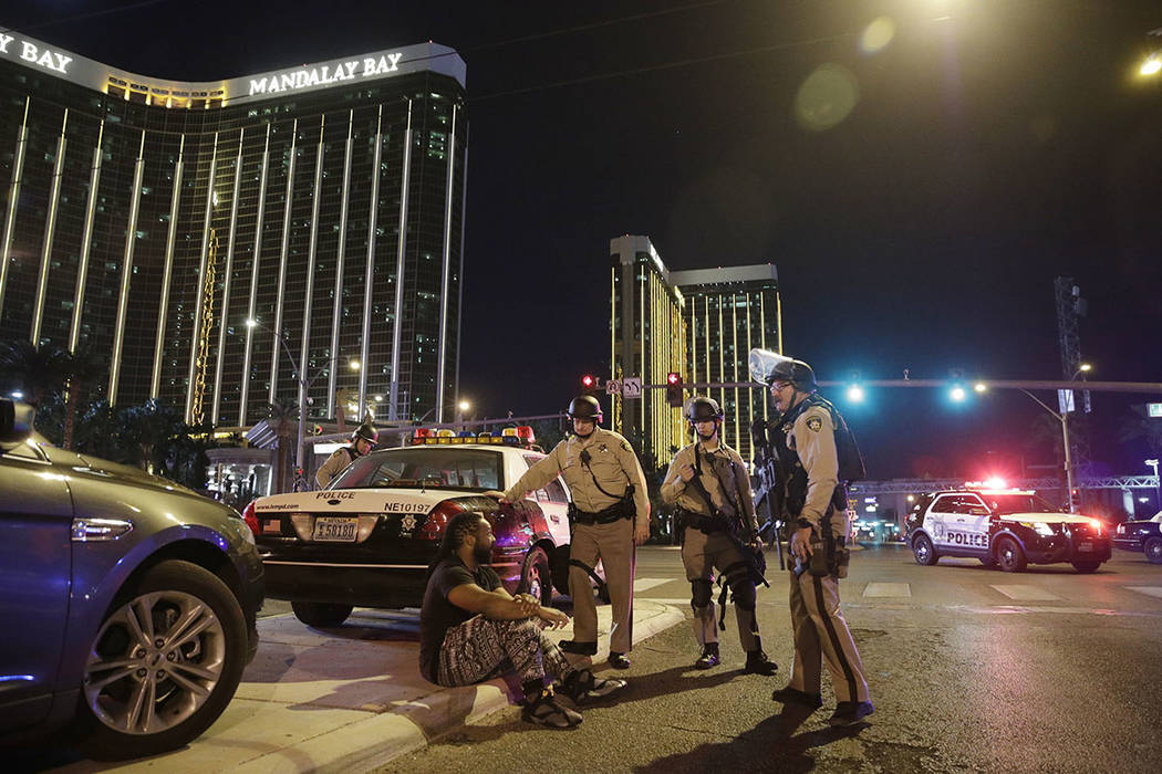 Police officers stand at the scene of a mass shooting near Mandalay Bay on the Las Vegas Strip on Oct. 1, 2017. (AP Photo/John Locher)