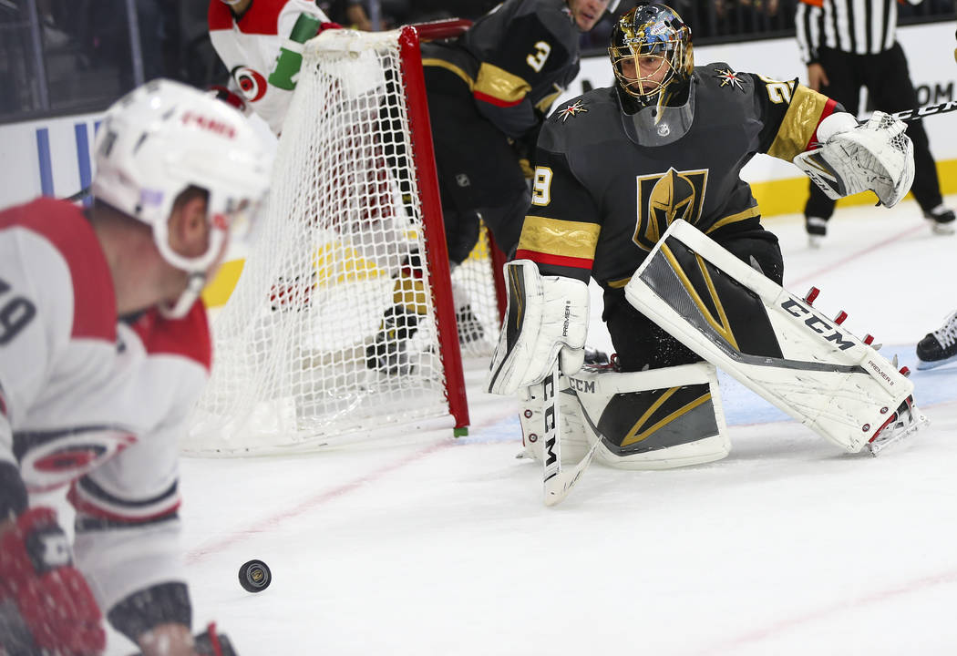 Golden Knights goaltender Marc-Andre Fleury (29) blocks a shot from Carolina Hurricanes left wing Micheal Ferland, left, during the second period of an NHL hockey game at T-Mobile Arena in Las Veg ...