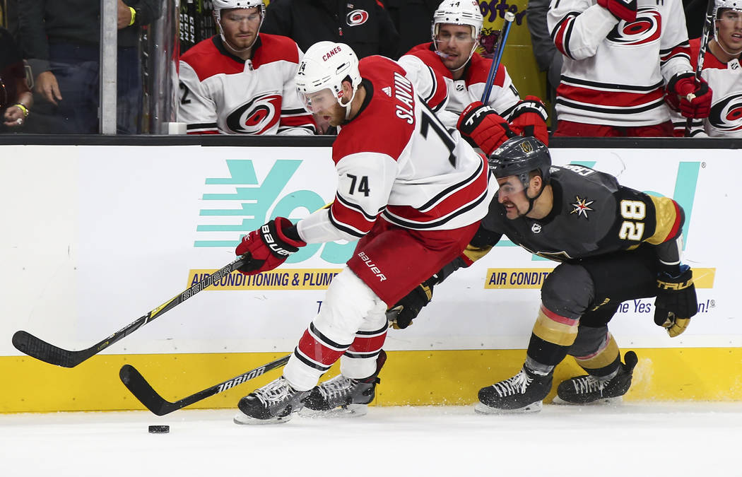 Golden Knights left wing William Carrier (28) tries to get the puck from Carolina Hurricanes defenseman Jaccob Slavin (74) during the third period of an NHL hockey game at T-Mobile Arena in Las Ve ...