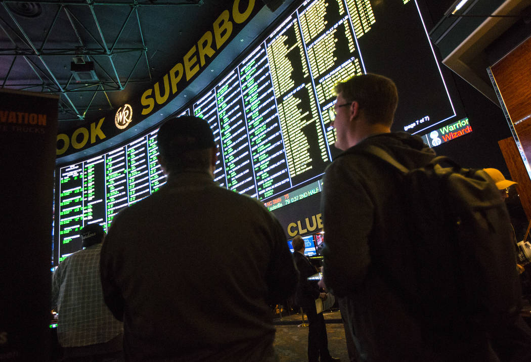 Bettors look at the display of prop bets for the Super Bowl at the Westgate Superbook in Las Vegas on Thursday, Jan. 24, 2019. The sportsbook posted 442 two-way props and more than 1,000 betting o ...