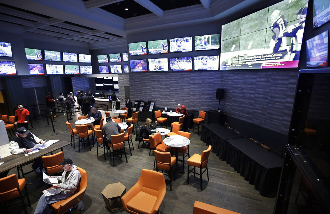 In this Monday, Jan. 28, 2019 photo, patrons visit the sports betting area of Twin River Casino in Lincoln, R.I. New England Patriots fans are gearing up for Super Bowl 53 by betting on the team t ...