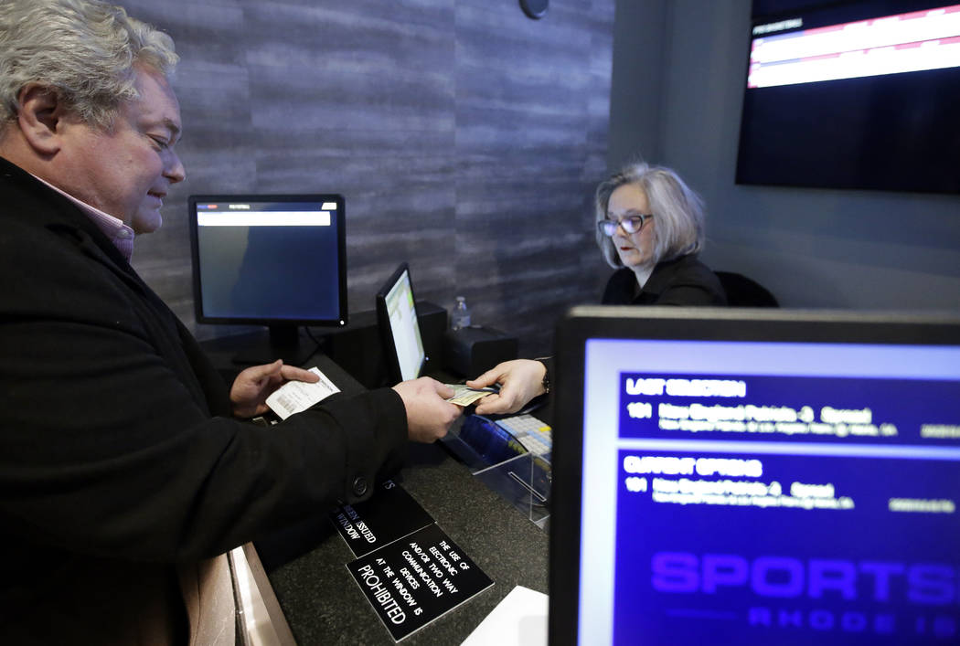 In this Monday, Jan. 28, 2019 photo, Rhode Island state Rep. William O'Brien places a $100 bet at Twin River Casino in Lincoln, R.I., on the New England Patriots NFL football team to win over the ...