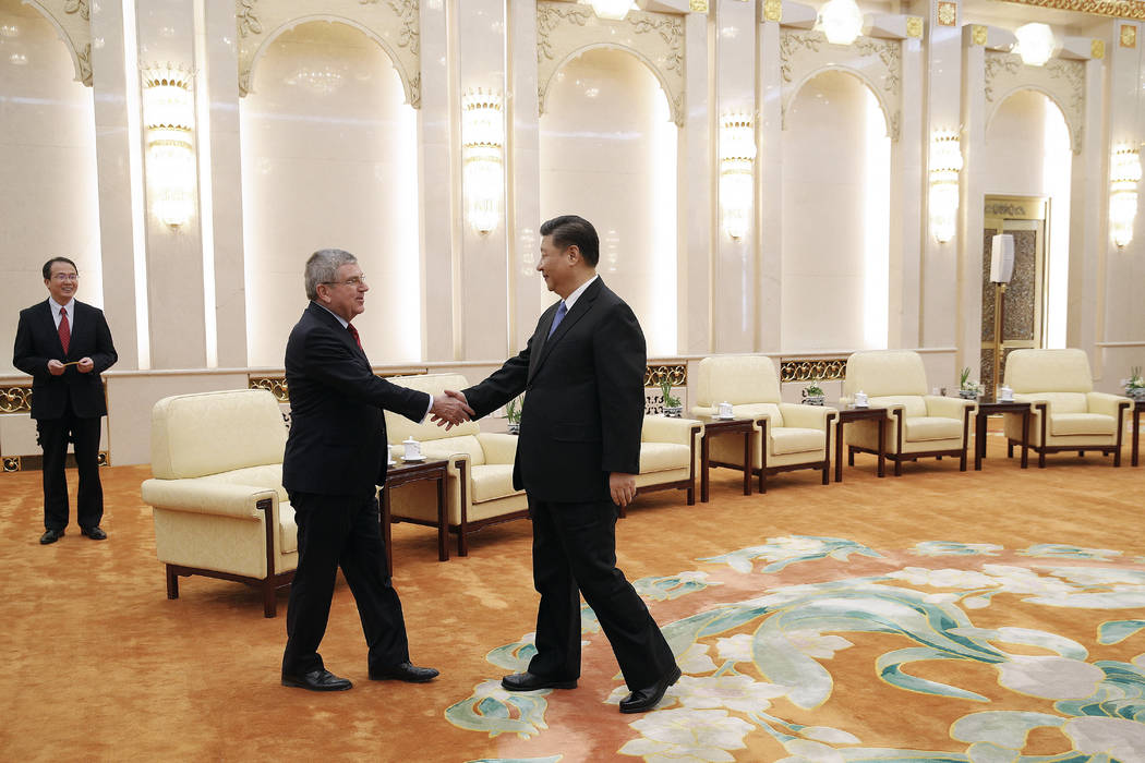 International Olympic Committee (IOC) President Thomas Bach, left, shakes hands with Chinese President Xi Jinping before proceeding to their meeting at the Great Hall of the People in Beijing, Thu ...