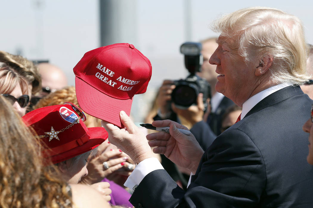 "In this Aug. 23, 2017 file photo, President Donald Trump hands a signed ""Make America Great Again,"" hat back to a supporter in Reno, Nev. An award-winning cookbook author and California restaurant ..."