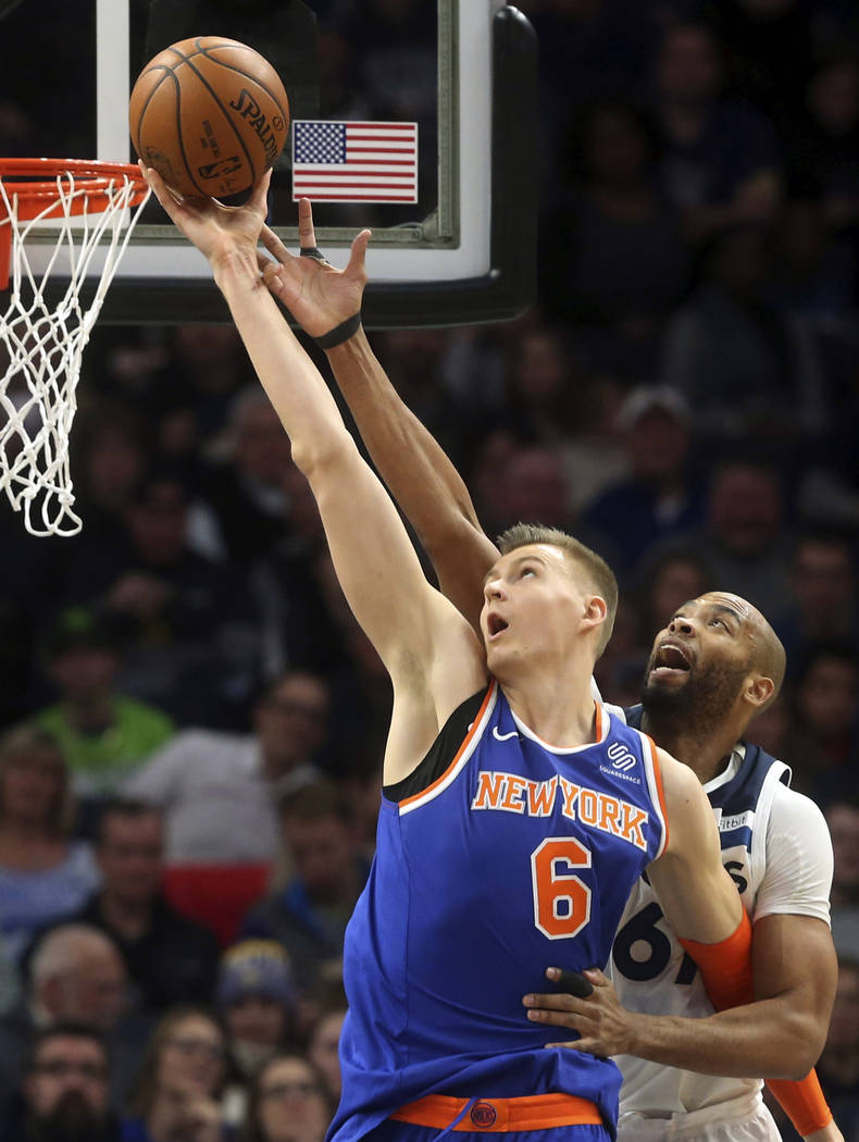 In this Jan. 12, 2018, file photo, New York Knicks' Kristaps Porzingis, left, of Latvia, outreaches Minnesota Timberwolves' Taj Gibson as he lays up the ball in the first half of an NBA basketball ...