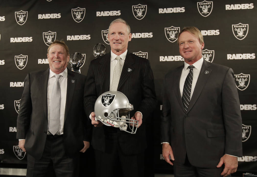 Mike Mayock, center, poses for photos with Oakland Raiders owner Mark Davis, left, and head coach Jon Gruden at a news conference announcing Mayock as the team's general manager in Oakland, Calif. ...
